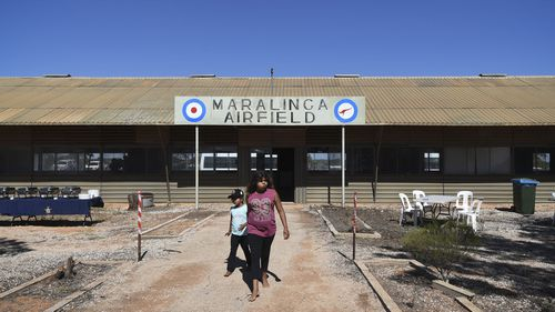 Aboriginal children walk near the Maralinga Airfield terminal, which was the scene of British atomic weapons testing from 1952 to 1967. (AAP)
