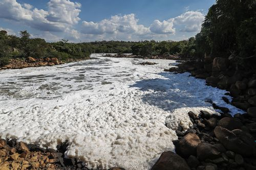 Foam flows over the surface of the Tiete River in Salto, Sao Paulo state, Brazil, Wednesday, Oct. 13, 2021.