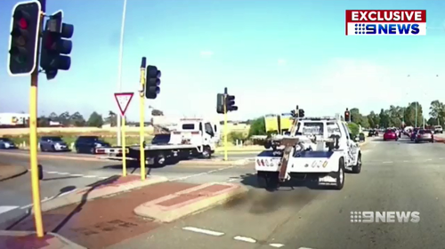 Footage exclusively obtained by 9News shows two tow competing tow truck companies run a red light, with one mounting the curb to beat each other to a crash job.