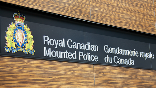 A sign for the Royal Canadian Mounted Police in English and French along with the crest of the RCMP.