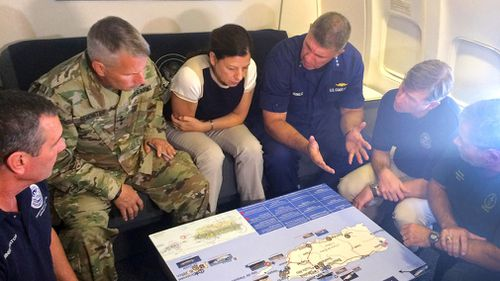 Acting Homeland Secretary Elaine Duke, center, is briefed on the Hurricane Maria response during a flight to Puerto Rico. (AP)