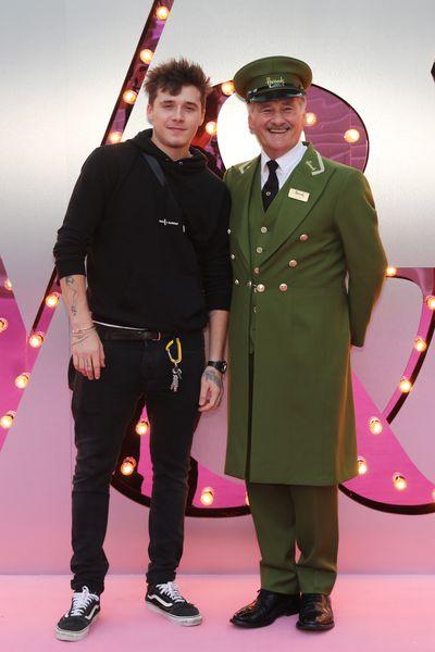 Brooklyn Beckham posing with the Harrods Green Man