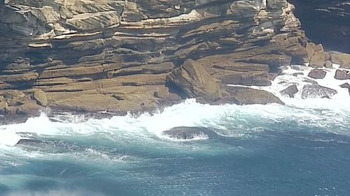 Two of the men managed to swim to rocks and hang on to a cliff face. (9NEWS)