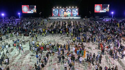 Security guards surround a pile of tables and chairs thrown by spectators at the Invitational Darts Challenge in Melbourne. (Getty)