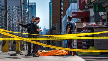 Police officers stand by a body covered on the sidewalk in Toronto.