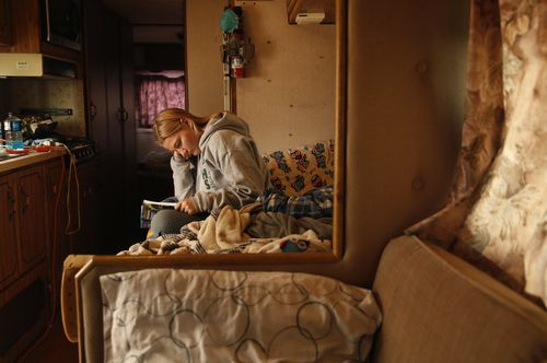 Arissa Harvey studies a chemistry book in an RV where she is living with her family in Paradise, California.