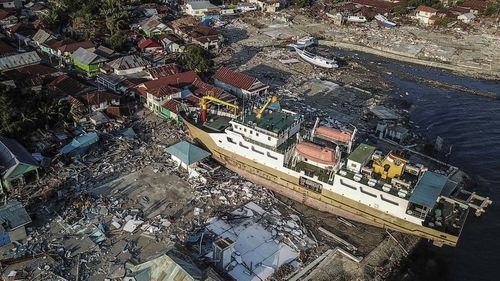 The impact of the earthquake and tsunami from above shows a ship dragged inland.