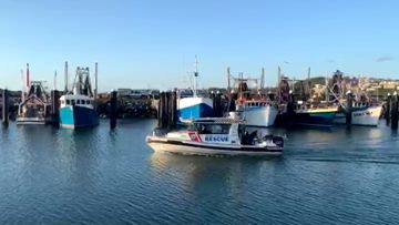 A boat returns to Coffs Harbour after a so-far unsuccessful search for two fishmen who did not return from their fishing trip.