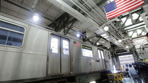 Members of the media witness a demonstration of new measures involving UV-C light technology to disinfect a subway car