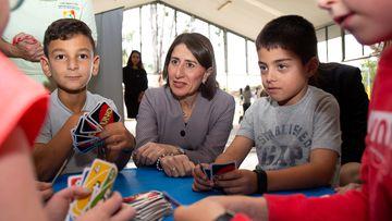 NSW Premier Gladys Berejiklian sits with primary school children.