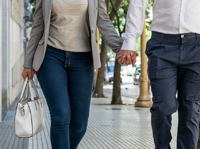 A young couple is walking down the street carrying luggage.
