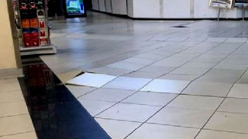 Tiles were dislodged from the floor of the Coles store. (9NEWS)