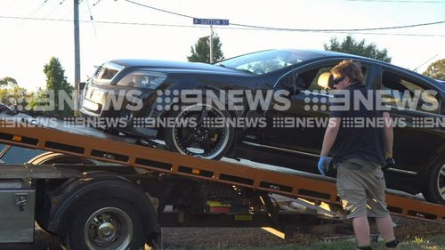 A tow truck driver watches as a black car is winched on to the back of a truck.