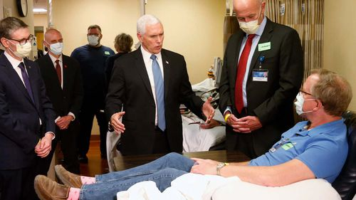 Vice President Mike Pence, center, visits a patient who survived the coronavirus and was going to give blood during a tour of the Mayo Clinic Tuesday, April 28, 2020, in Rochester, Minn.