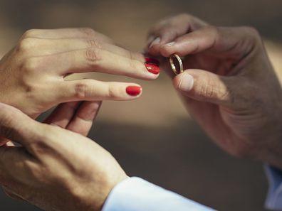 Groom putting wedding ring on finger of bride, close up