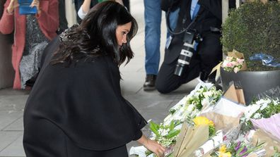 The Duchess places a bouquet of flowers, adding to the floral tribute.