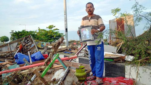 A man holds a family picture retrieved from a damaged house in Palu.