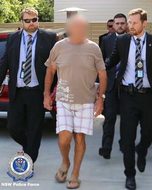 Detectives lead Chris Dawson away from a Gold Coast home this morning.