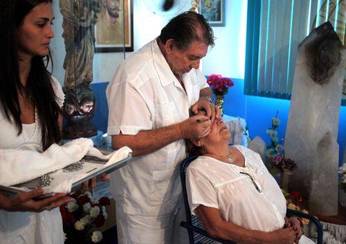 Joao Teixeira de Faria, known as John of God, uses a knife to perform a spiritual surgery on a woman's eyes.