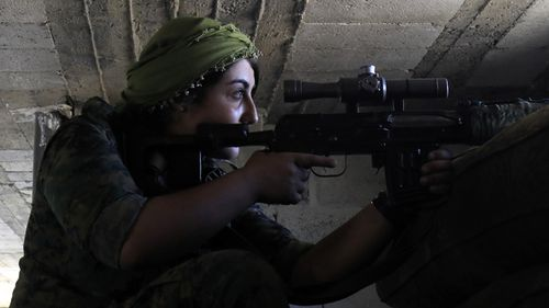 A female member of the Syrian Democratic Forces, a US-backed Kurdish-Arab alliance, holds a position inside a building in an area close to the Old City in the embattled northern Syrian city of Raqa on September 3, 2017, as they battle to retake the city from the Islamic State group. (AFP)