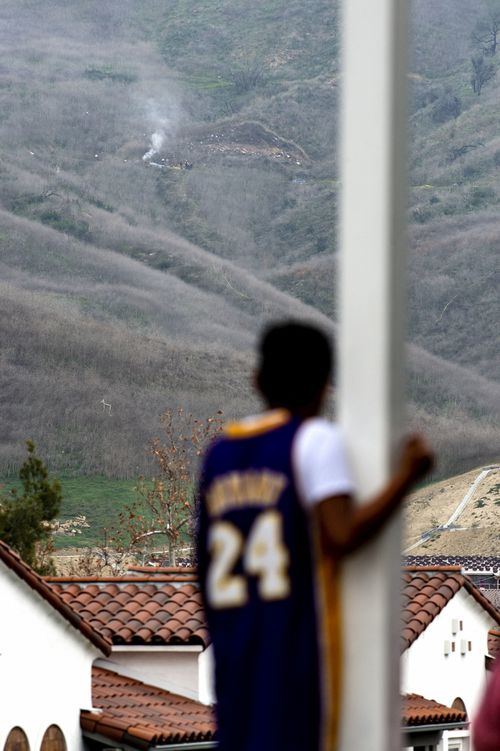 A young LA Lakers fan looks up to the hill where NBA legend Kobe Bryant was one of nine people killed in a helicopter crash.