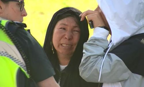 The victim's mum arrived at the scene, sitting on the street while she spoke with detectives.