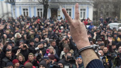 Mikheil Saakashvili shows the peace sign to supporters outside his apartment in Kiev. (AAP)