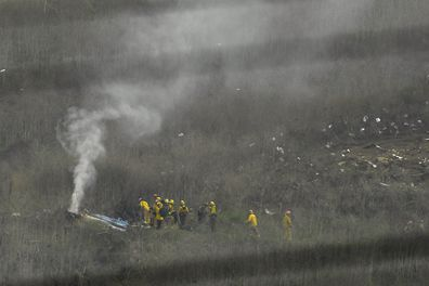 Firefighters work at the scene of a helicopter crash that killed former NBA basketball player Kobe Bryant, his 13-year-old daughter and seven other people on board.