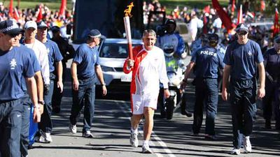 Ron Clarke runs with the torch during the Beijing Olympic torch relay in Canberra on 2008.