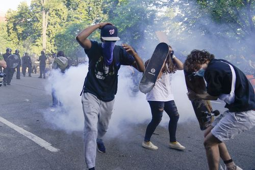 Demonstrators, who had gathered to protest the death of George Floyd, run from tear gas used by police to clear the street near the White House in Washington