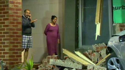 Amit Saraf and his pregnant wife inspect the damage to the home's exterior. (9NEWS)