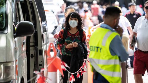 A woman wearing a face mask seen near the Overseas Passenger Terminal where the Norwegian Jewel cruise ship is moored at Circular Quay in Sydney, Friday, February 14, 2020.
