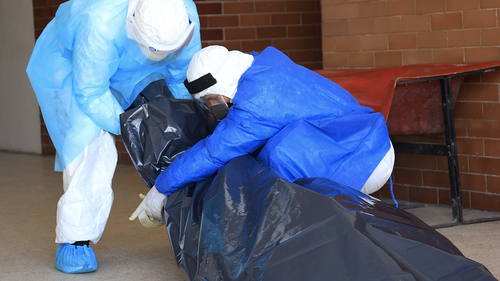 Personnel of Loreto Regional Hospital Felipe Santiago Arriola Iglesias wearing PPE suits wrap the corpse of COVID-19 victim in a plastic bag to take it to the morgue during coronavirus pandemic at on April 27, 2020 in Iquitos, Peru.