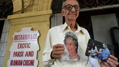 Huge royals fan Boman Kohinoor stands outside his restaurant holding photographs of the royal family.