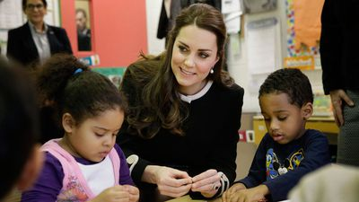 Preschoolers April, 4, left, and Sammy, 4, receive a helping hand from the British Royal. (AAP)
