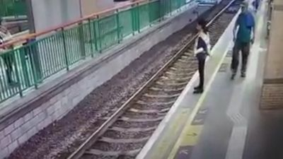 Woman shoved onto train tracks in unprovoked attack