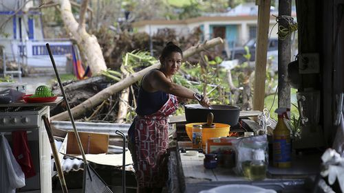 Margarita Burgos cooking outside over a wood fire, due to the lack of cover and electricity in Yabucoa. (AAP)