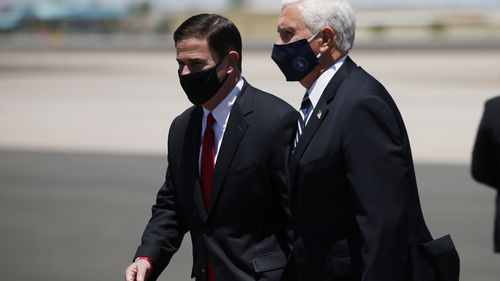 Vice President Mike Pence, right, walks with Arizona Gov. Doug Ducey, left, as the two head to a meeting to discuss the surge in coronavirus cases.