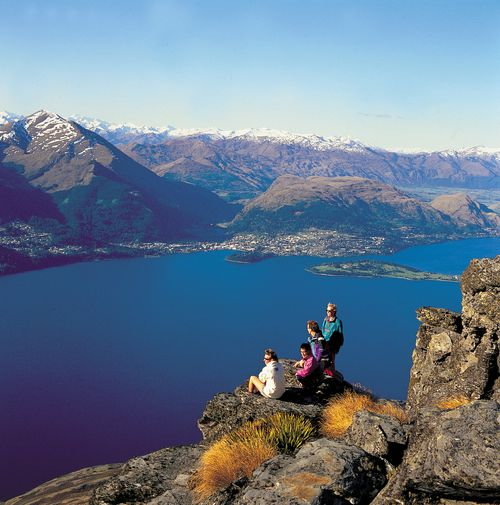 Hikers enjoy the view from Cecil Peak towards Queenstown, New Zealand