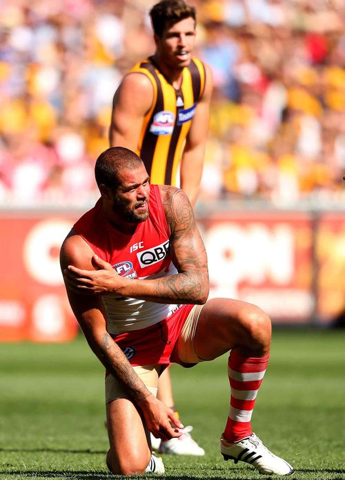 Lance Franklin of the Swans grabs his shoulder after a marking contest with Brian Lake of the Hawks. (Getty)