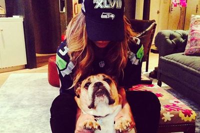 While John Legend posed with the players, wife Chrissy Teigen was getting their pet pooch into the Super Bowl spirit.