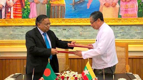 Myanmar's Union Minister for the Office of the State Counsellor Kyaw Tint Swe, right, and Bangladesh Foreign Minister Abdul Hassan Mahmud Ali exchange notes after signing the Arrangement on Return of Displaced Persons from Rakhine State in Naypyitaw, Myanmar. (AAP)