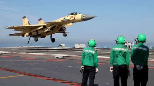 A warplane lands on the flight deck of the Liaoning. The aircraft carrier may become a test bed for an electromagnetic launch system.
