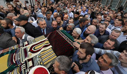 People carry a coffin with the body of late Russian journalist Orkhan Dzhemal during a funeral ceremony for him outside the Moscow Cathedral Mosque in Moscow