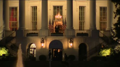 Donald Trump stands on a balcony outside the White House.