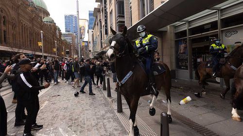 Mounted police are pelted with bottles during an anti-lockdown protest in Sydney's CBD last week.