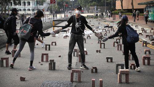 Protestors move bricks as they barricade a road near the Hong Kong Polytechnic University in Hong Kong.