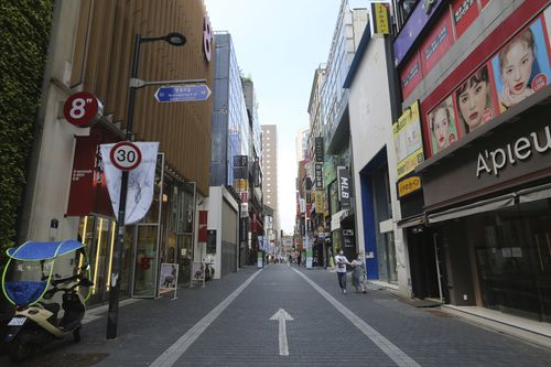 A couple wearing face masks to help protect against the spread of the coronavirus walks along on a nearly empty shopping street in Seoul, South Korea.