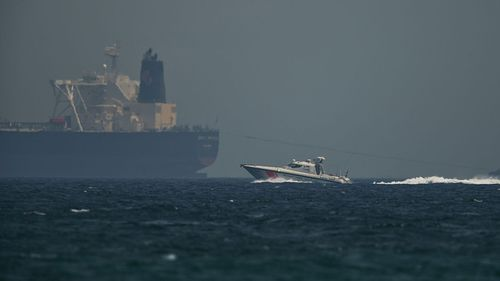 """An Emirati coast guard vessel passes an oil tanker off the coast of Fujairah, United Arab Emirates. Saudi Arabia said two of its oil tankers were sabotaged off the coast of the United Arab Emirates near Fujairah in attacks that caused """"significant damage"""" to the vessels."""