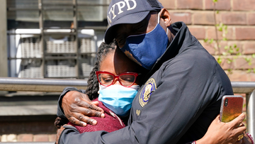 A police officer hugs a community leader outside the building where a man shot the mother of his child and two of her daughters dead before turning the gun on himself, Tuesday, April 6, 2021, in the Brownsville neighborhood of the Brooklyn borough of New York.